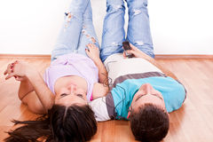 Happy couple on floor listening music Stock Photo