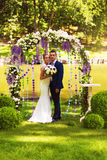 Happy couple in flower arch. On nature Stock Photos