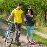 Happy couple with flowers & bicycle walking Royalty Free Stock Photo