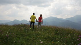 Happy couple on the flowers field into the mountains. During the day stock video footage