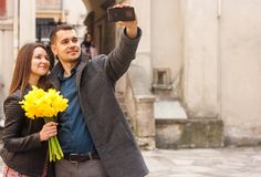 Happy couple with flowers making selfie in the street. Copy space stock images