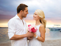 Happy couple with flowers over beach background Stock Photos