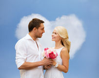 Happy couple with flowers over heart shaped cloud. Holidays, love, people and dating concept - happy couple with bunch of flowers over blue sky and heart shaped Royalty Free Stock Image