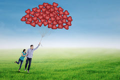Happy couple flying with heart shaped balloons Stock Photography