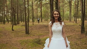 Happy couple in a forest in the fresh air. The groom goes to the bride with a beautiful bouquet. The bride stood still. Waiting stock video