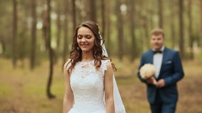 Happy couple in a forest in the fresh air. The groom goes to the bride with a beautiful bouquet. The bride stood still. Waiting stock video footage