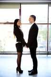 Happy couple in formal cloth. Full length portrait of a happy couple in formal cloth standing in office Stock Photos