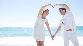 Happy couple forming heart shape with their hands Stock Photography
