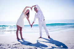 Happy couple forming heart shape with their hands Stock Photos