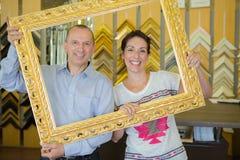 Happy couple found antique gold photo frame Stock Photos