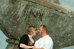 Happy Couple at Fountain. Happy Couple in front of a fountain on their honey moon. They are holding each other and he is telling her how much he loves her stock photos