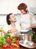 Happy couple with fresh vegetables and greens in home kitchen Stock Images