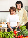Happy couple with fresh vegetables and greens in the kitchen Royalty Free Stock Photography