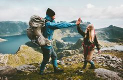 Happy couple friends giving five hands on the top of mountain royalty free stock image
