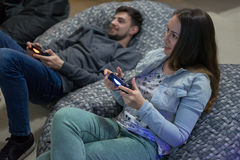 Happy couple friends playing video games with joystick sitting on Bean bag chair Stock Photos
