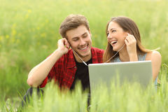 Happy couple or friends sharing music from a laptop Royalty Free Stock Image