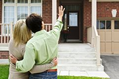 Happy couple in front of home Stock Photos