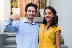 Happy couple in front of new house showing keys. Happy Hispanic couple in front of new house showing keys stock photography