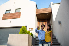 Happy couple in front of new house showing keys. Happy Hispanic couple in front of new house showing keys stock images
