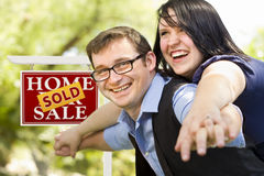 Happy Couple in Front of Sold Real Estate Sign Stock Image