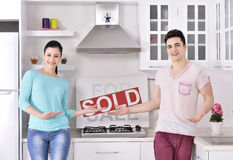 Happy Couple in Front of Sold Real Estate Sign Royalty Free Stock Photography