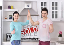 Happy Couple in Front of Sold Real Estate Sign Royalty Free Stock Image