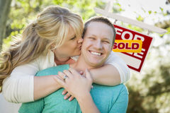 Happy Couple In Front Sold Real Estate Sign Royalty Free Stock Photos