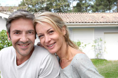Happy couple in front of their new house Stock Images