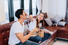 Happy couple funny girlfriend makeup boyfriend. Watching television comedy show sitting on sofa comfortable couch in living room at home Stock Images