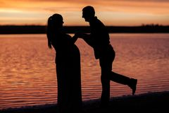 Silhouette of man with his pregnant wife on the beach at sunset stock images