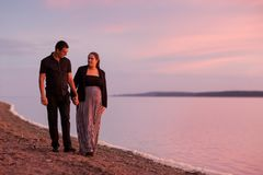 Romantic young couple holding hands and walkind in the coast at sunset Stock Images