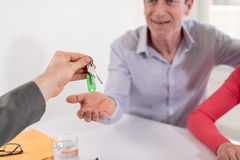 Happy couple getting house keys from realtor Stock Photo