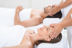 Happy couple getting massage at spa. Getting rid of our stress. Cropped shot of husband and wife lying together on massage tables and receiving head massages Royalty Free Stock Photography