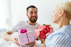 Happy couple with gift box in bed at home Royalty Free Stock Photo