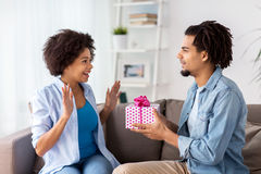 Happy couple with gift box at home Royalty Free Stock Images