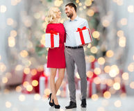 Happy couple with gift boxes over christmas lights Royalty Free Stock Image