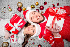 Happy couple with gift boxes. Happy couple in santa hats lying on floor with gift boxes Royalty Free Stock Photography