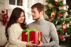 Happy couple with gift at home on background of Christmas tree Stock Photo