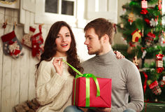 Happy couple with gift at home on background of Christmas tree Stock Image