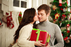 Happy couple with gift at home on background of Christmas tree Royalty Free Stock Photography