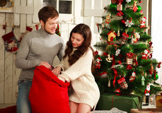 Happy couple with gift at home on background of Christmas tree Stock Photography