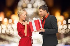 Happy couple with gift over christmas tree lights Royalty Free Stock Images