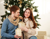 Happy couple with gifts on background of Christmas tree at home Stock Images