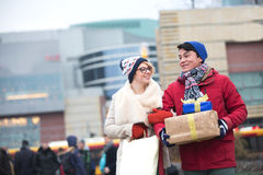Happy couple with gifts and shopping bags walking in city during winter Stock Image