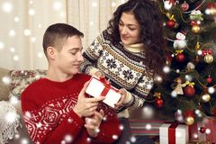 Happy couple give gifts in christmas decoration at home. New year eve, ornated fir tree. Winter holiday and love concept. Stock Images