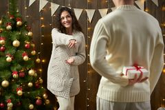 Happy couple give gifts in christmas decoration, sitting on floor in dark wooden interior with lights. Romantic evening and love c. Oncept. New year holiday Royalty Free Stock Photo