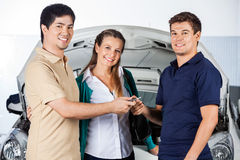 Happy Couple Giving Car Keys To Technician. Portrait of happy couple giving car keys to technician at auto repair shop Stock Photography