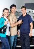 Happy Couple Giving Car Keys To Technician. Portrait of happy couple giving keys to technician while standing in front of car at auto repair shop Stock Image