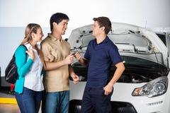 Happy Couple Giving Car Keys To Technician Royalty Free Stock Photo
