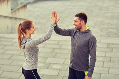 Happy couple giving high five outdoors Stock Images